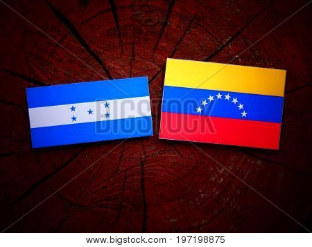 Honduran Flag With Venezuelan Flag On A Tree Stump Isolated