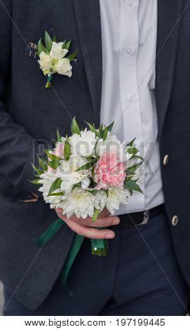 Bouquet in the hands of groom.