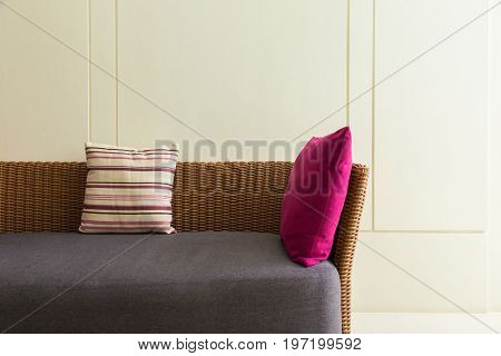 section of empty modern design wicker sofa with 2 pillows and empty wall room for text or copyspace