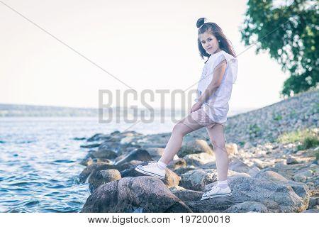Portrait of little girl walking on berth near sea