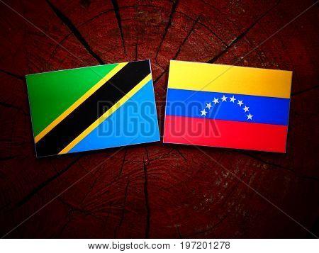 Tanzanian Flag With Venezuelan Flag On A Tree Stump Isolated