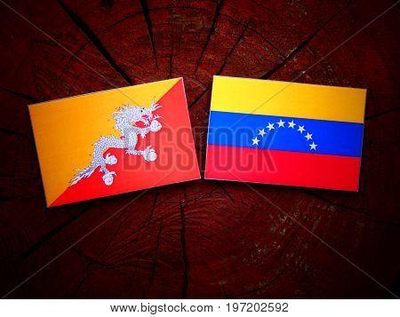 Bhutan Flag With Venezuelan Flag On A Tree Stump Isolated