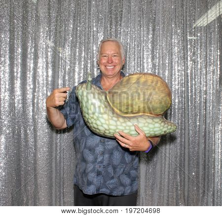 A man holds an inflatable snail while smiling and pointing in a photo booth with a silver sequin background.