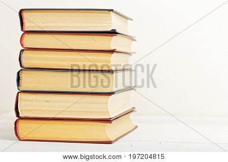 A Stack Of Old Books On A Light Beige Background