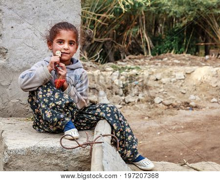 Leh, Ladakh, India, July 14, 2016: young girl is playing with a necklace near her house in Leh, India