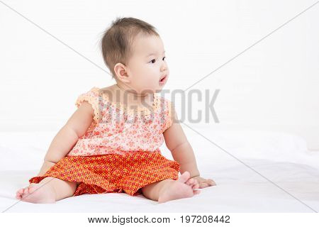 Portrait Of A Little Adorable Infant Baby Girl Sitting On The Bed And Looking To The Right Side With