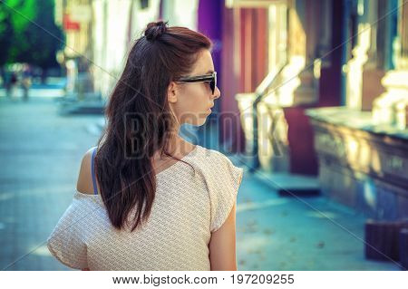 Portrait of pretty young brunette woman with long hair, wearing sunglasses, walking along the street on a sunny day. Cross processed image.