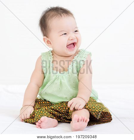 Portrait Of A Little Adorable Infant Baby Girl Sitting On The Bed And Smiling With Copyspace