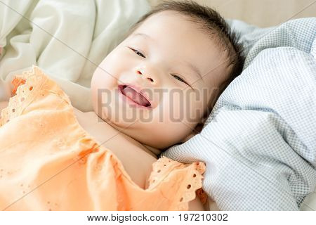 Portrait Of A Little Adorable Infant Baby Girl Lying On Back On Blanket And Looking In Camera Indoor