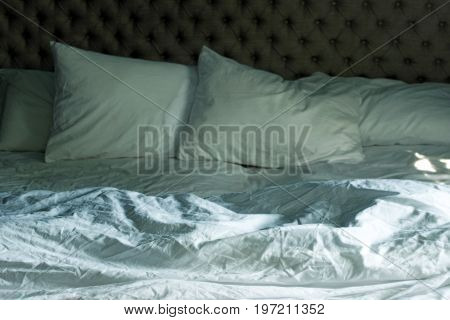 Empty, unmade bed with wrinkled sheets, head board and pillows.