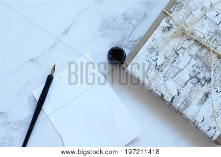 Marble desk with birch paper wrapped gift, bottle of ink and calligraphy pen with blank notecard. Copy space.