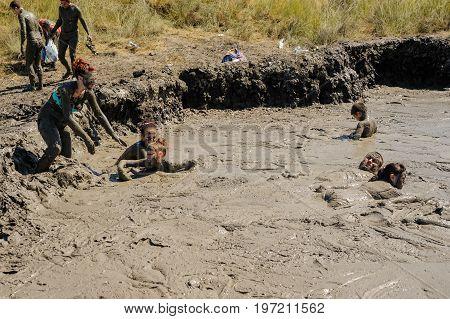 Kuchugury, Russia - July 16, 2017: Azov scorching heat mud volcano. People take procedures with healing mud