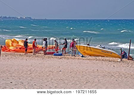 SOUSSE, TUNISIA - APRIL 28, 2008: Unidentified people are trying to open parachute on the windy weather