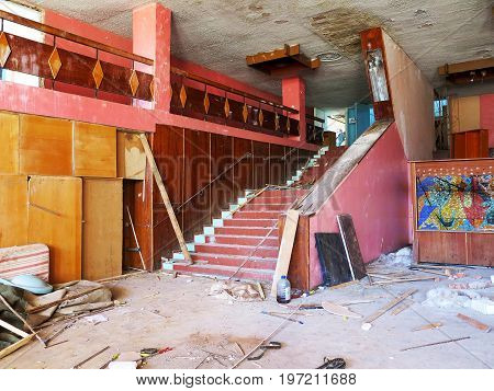 Old staircase in interior of an abandoned and ruined building of cultural center of resort. Destroyed old staircase in looted interior of dying abandoned buildings