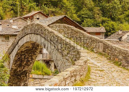 a   characteristic  bridge  of a piedmontese alpine village / a   characteristic  bridge  of a piedmontese alpine villagea romanesque bridge made of donkey back of of the 17th century at the entrance to the village of Fondo in Piedmont Italy