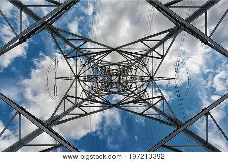 under a high voltage pylon on blue cloudy sky background