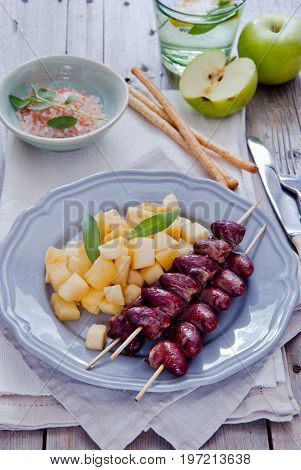 Grilled chicken hearts on skewers with stewed apples on a grey plate