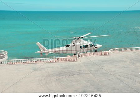 white helicopter lands on a helipad near the sea. Helicopter takeoff.