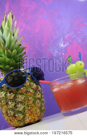 Pineapple fruit with blue  sunglasses drinks fruity cocktail