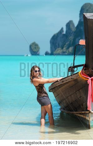 Young girl in sunglases near traditional longtail boat on Phi Phi islands, Thailand. Vacation concept