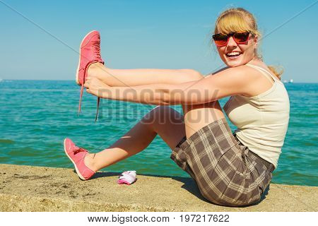 Summer vacation relax and traveling concept. Young tourist woman hiker relaxing on sea shore enjoying sunlight tying shoelace