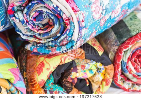 relaxation, coiziness, rest concept. stack from four different rags rolled up into tube has various colors. Top one is blue and decorated by images of flowers and petals