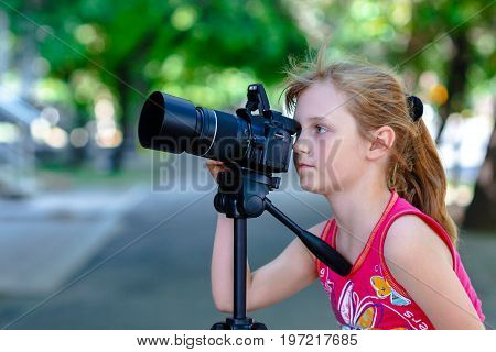 Little girl photographer looking into the camera and make the photos with professional SLR camera using tripod
