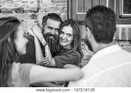 Couple of handsome bearded men with long beard and stylish hair and blonde pretty cute sexy woman or girl embracing and smiling to they friends on summer sunny day on stony wall background