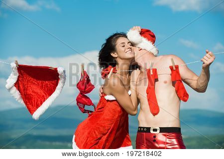 Laundry and dry cleaning. Christmas man and woman family. Couple of happy man and girl hanging clothes for drying. New year guy with muscular body on blue sky. Xmas red costume on rope with pins.