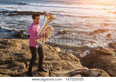 Young musician play the Tuba on rocky sea coast during surf. Trumpet.