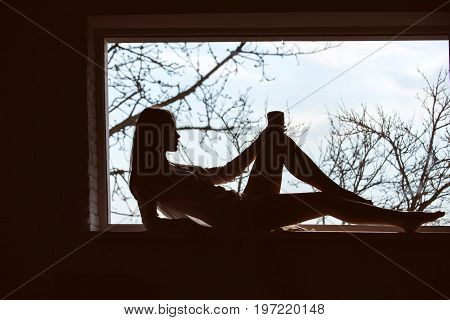 Beauty and fashion. Silhouette of sexy woman on window sill. Fashion model posing. Woman with in dress laying at window. Girl drink from cup in morning.