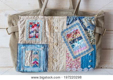 hobby, art, fashion concept. womanish velvet hand bag warm colors sheathed satine textile decorated satine textile, buttons and square applications with sky and clouds
