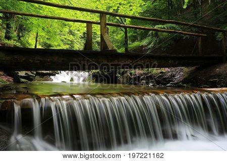 bridge over small watrfall on mountain river