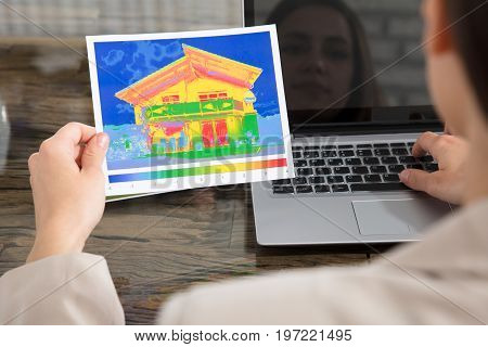 Close-up Of A Person Detecting Heat Loss Of A House Using Laptop On Desk