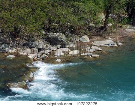 Tumble water flowing through the rocks and rocks in the mountainous river