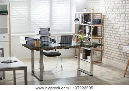 Stack Of Folders On Office Desk With Laptop In Modern Office
