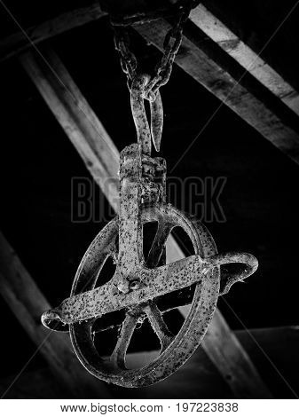 An antique pulley hangs from a shed. It's metal has become oxidized. The photo is in black and white.
