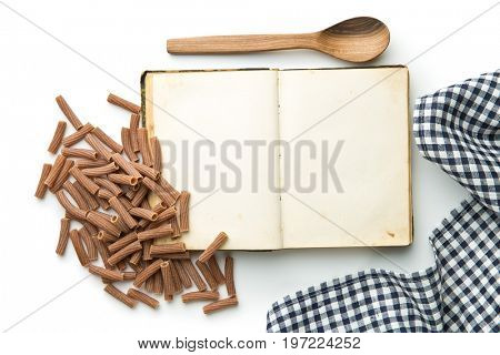 Blank recipe book and italian pasta isolated on white background. Top view.