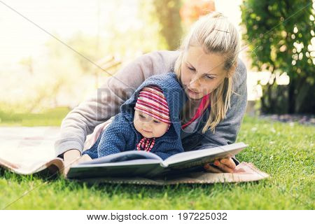 mother reading a book to baby in backyard garden on blanket