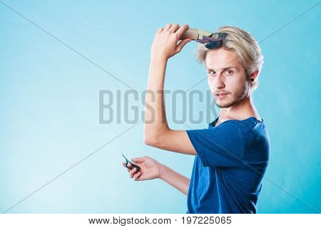 Hairdo changing hairstyle concept. Cool male hairstylist making self trendy haircut fashion blonde metrosexual model going to shave his long hair using shaver and scissors