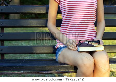 The girl on a bench in the park with a book in her lap. A student in the park reading a book