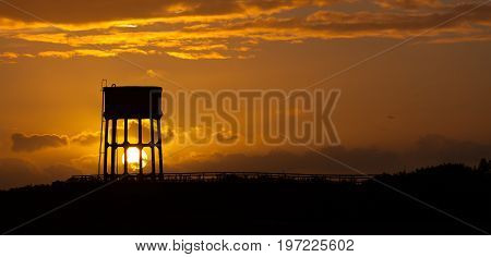 Sunset behind a water tower in the commune known as Sandy Lane, Swansea, Gower, South Wales.