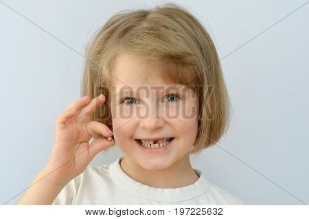 child, kid, shows the fallen baby tooth.
