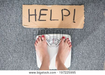 Elevated View Of Help Sign On Cardboard With Woman's Feet On Weighing Scale