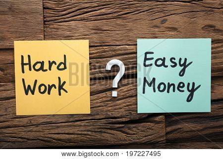 Closeup of hard work and easy money on sticky notes amidst question mark on wood