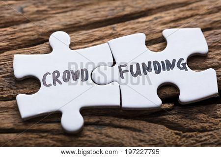 Closeup of connected crowd funding jigsaw pieces on wood