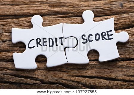 Closeup of connected credit score jigsaw pieces on wood