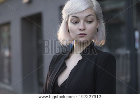 Blond lovely model in sunset light outdoors closeup portrait in black suit and with ear tunnels. no makeup perfect skin