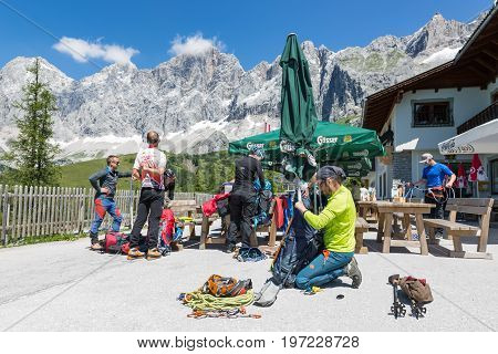 DACHSTEIN MOUNTAINS AUSTRIA - JULY 17 2017: Alpinists preparing their equipment for rock-climbing in Dachstein Mountains of Austria