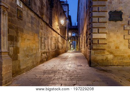 Narrow medieval street Carrer del Bisbe and bridge of sighs in the Gothic quarter of Barrie at dawn. Barcelona. Spain.